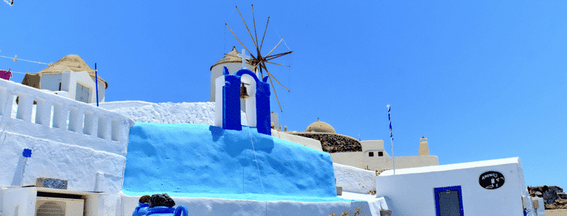 photo of a windmill in greece atop beautiful greek architecture and the beautiful greek landscape