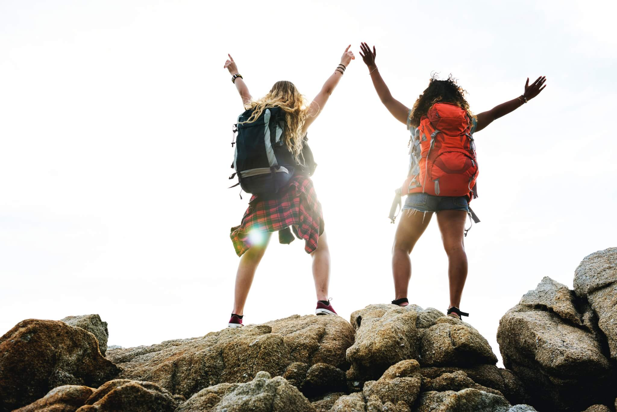 Two women on a hill with travel backpacks on.