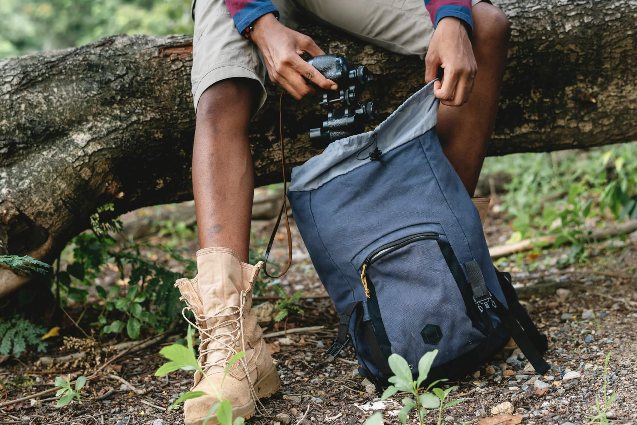 A man pulling a camera out of a backpack.
