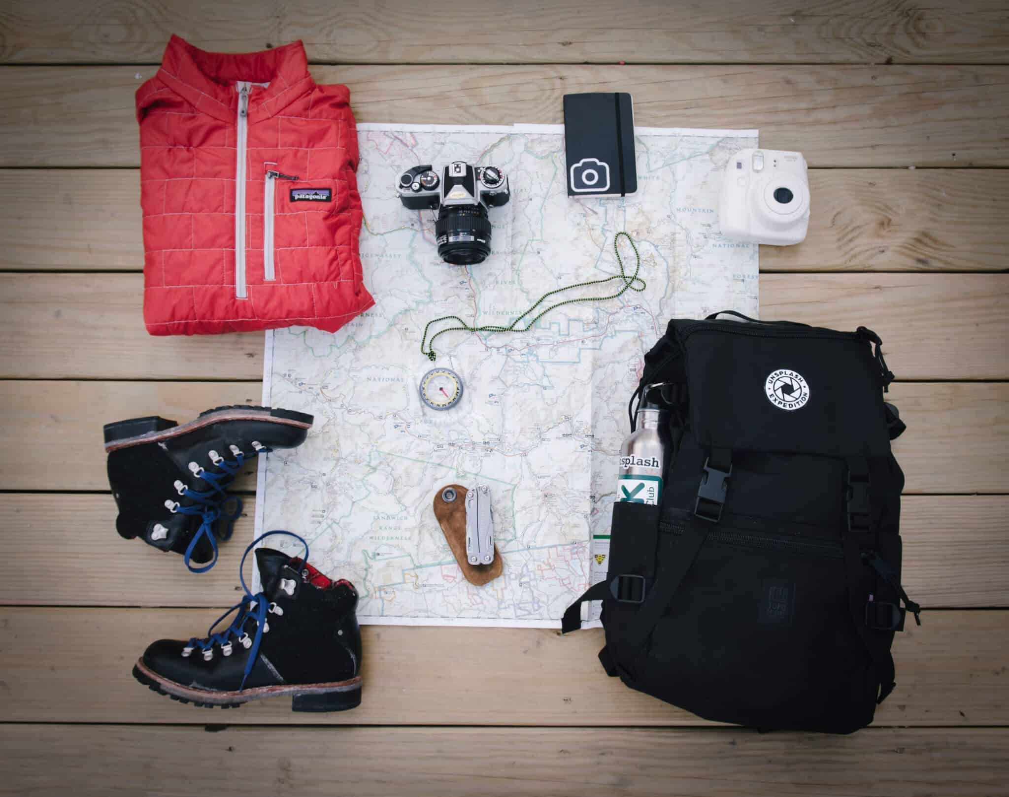 A flatlay with a travel backpack and other travel accessories like a compass and map.