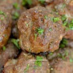 Italian meatballs piled in a serving dish garnished with parsley.