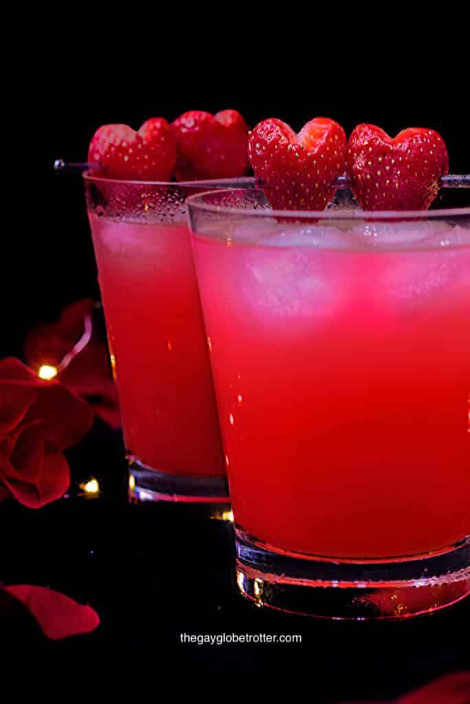 Love potion drinks topped with fresh strawberries surrounded by rose petals.