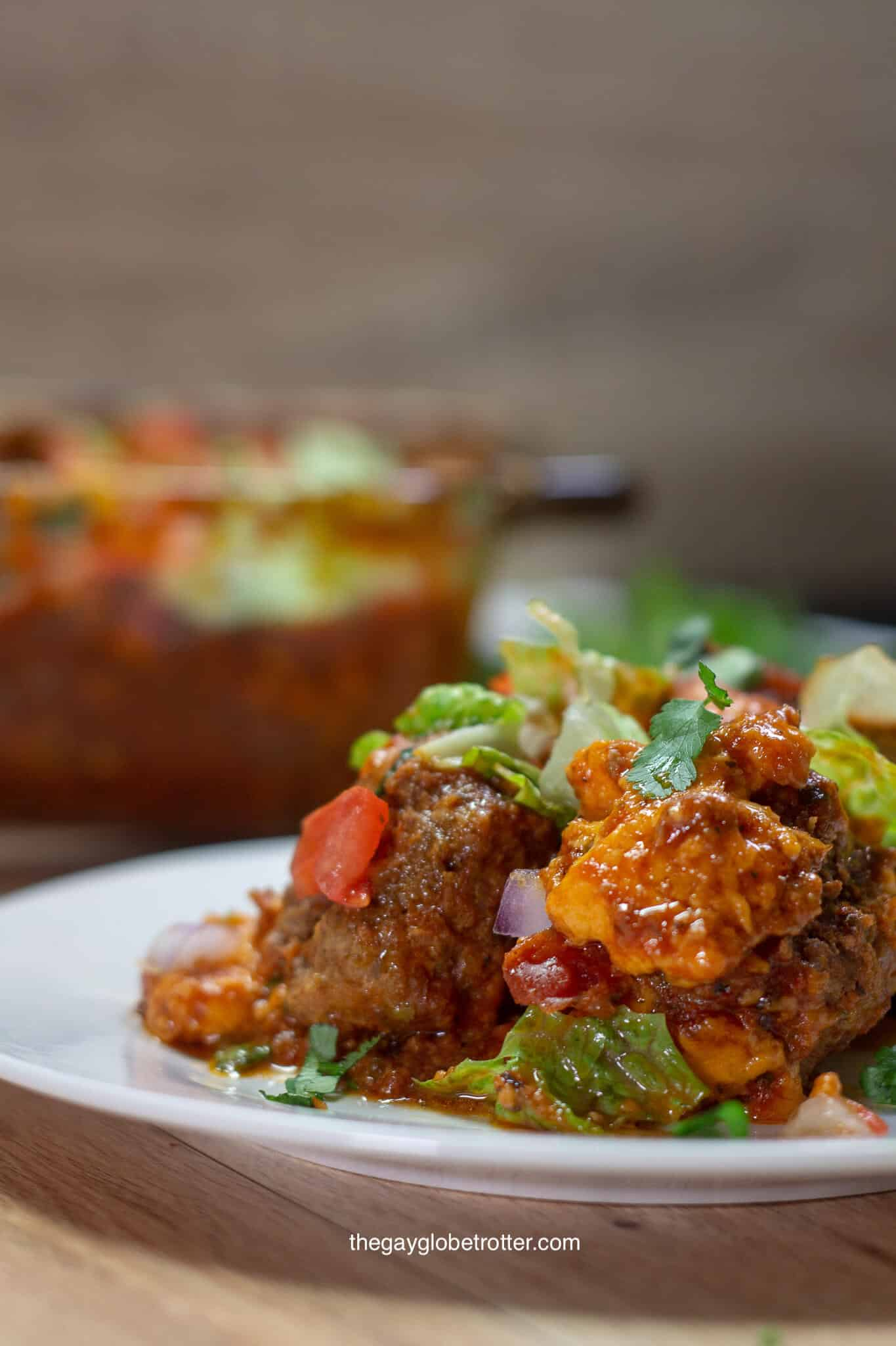 A plate of taco meatball casserole topped with tomatoes, lettuce, and cheese.