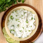 An overhead shot of cilantro lime rice surrounded by limes and cilantro.