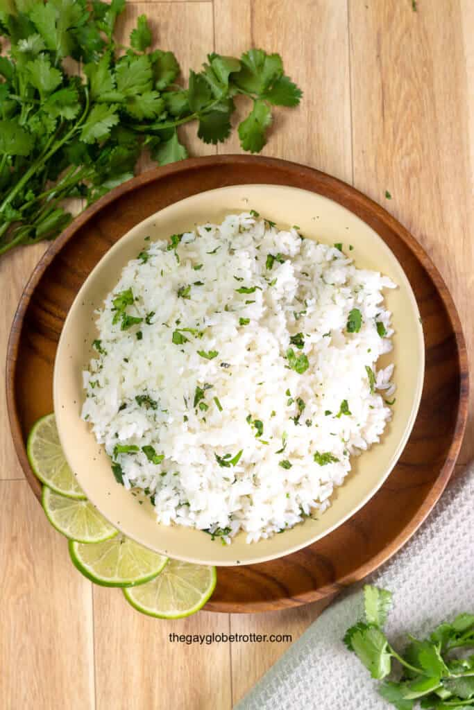 An overhead shot of cilantro lime rice surrounded by lime and cilantro.