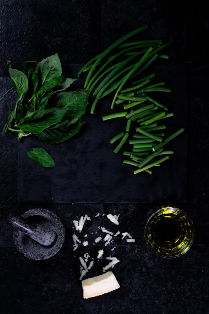 A working surface with ingredients for garlic scape pesto like basil and garlic scapes.