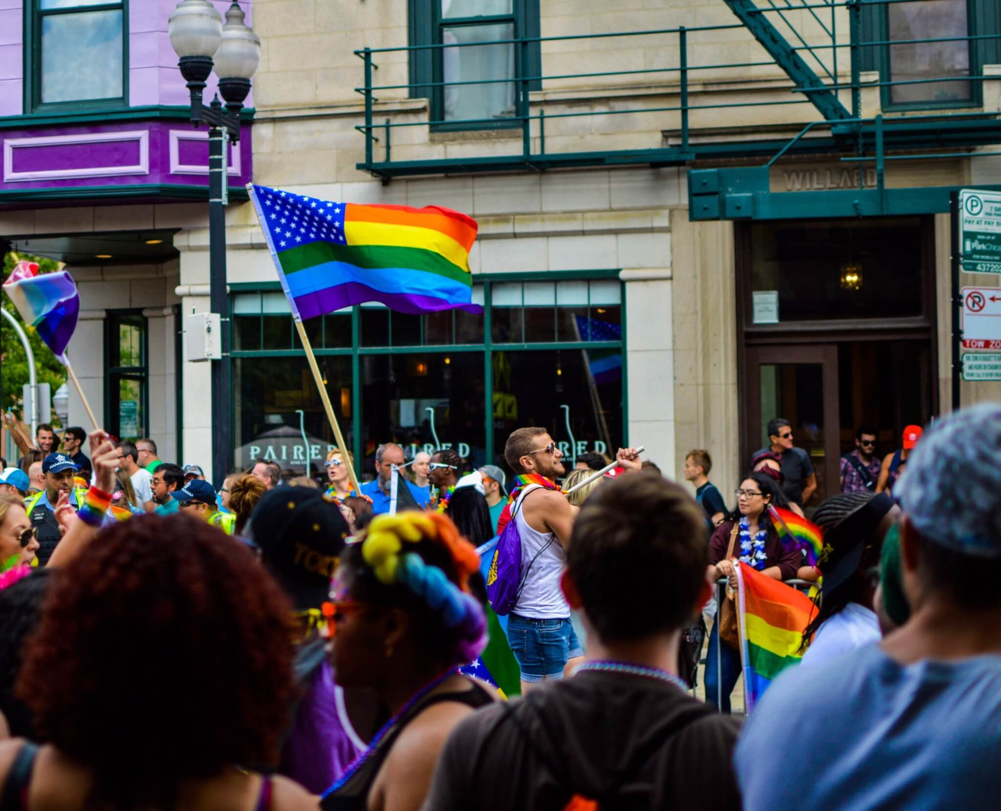 People waving a rainbow flag at ceremony.