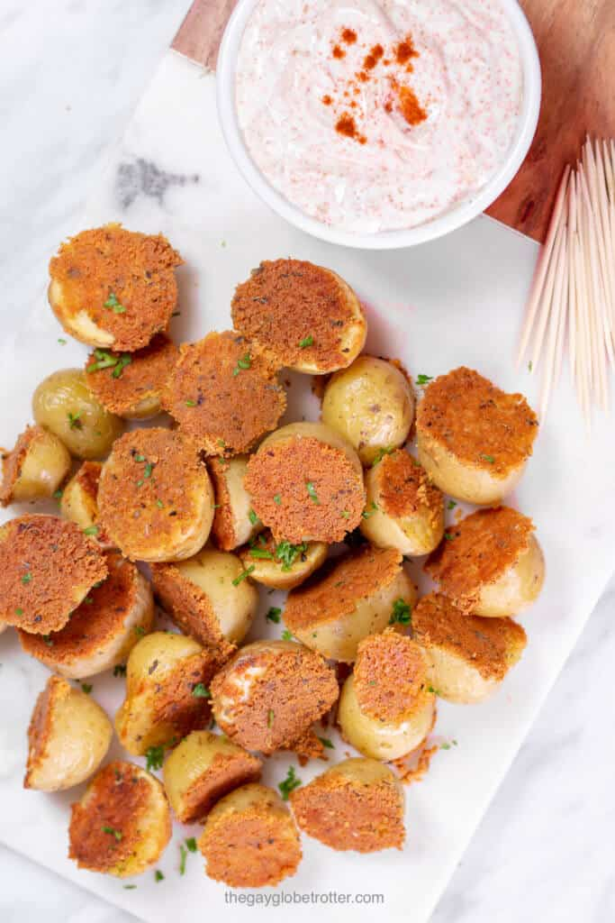 A platter of crispy parmesan roasted potatoes next to some chili sour cream dip and toothpicks.