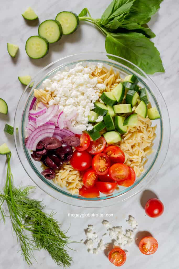 A bowl of Greek orzo pasta salad ready to be tossed.