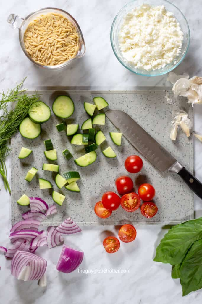 A cutting board filled with ingredients for orzo pasta salad like tomatoes, red onions, and cucumbers.
