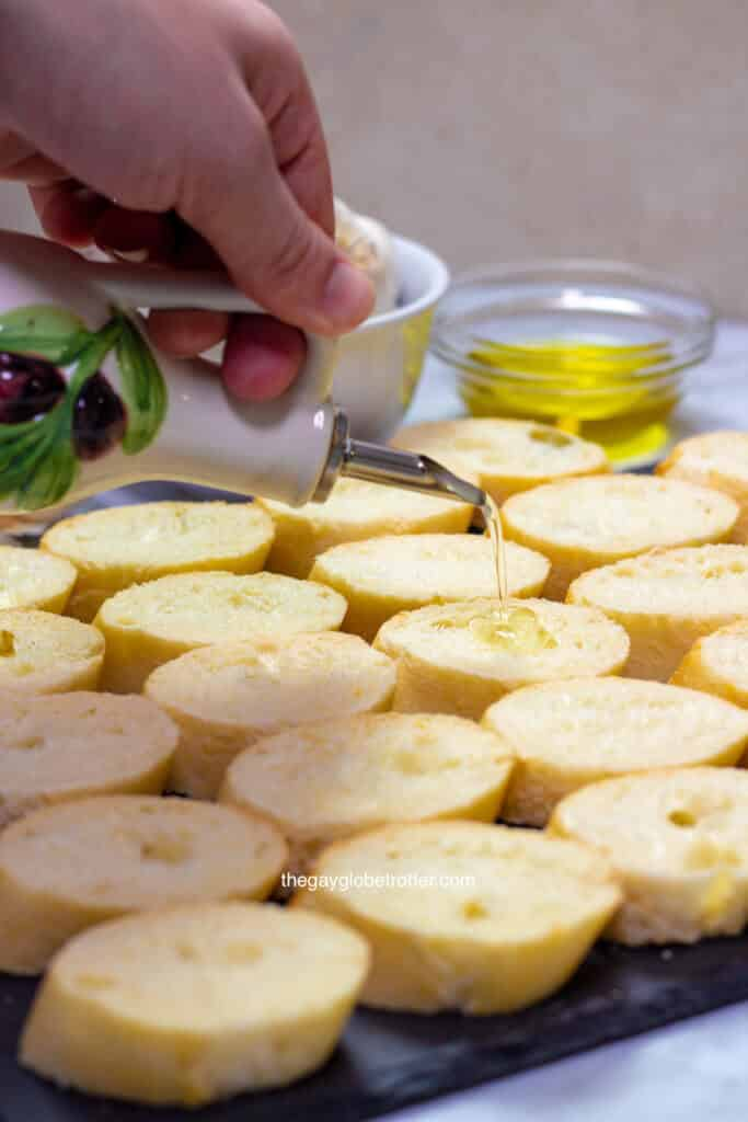 A hand pouring olive oil onto crostini slices.