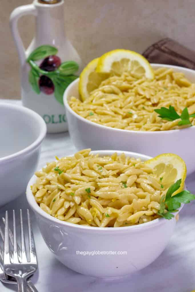 A bowl full of parmesan lemon orzo garnished with lemon.
