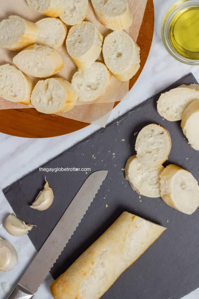 A knife slicing a baguette into crostini pieces.