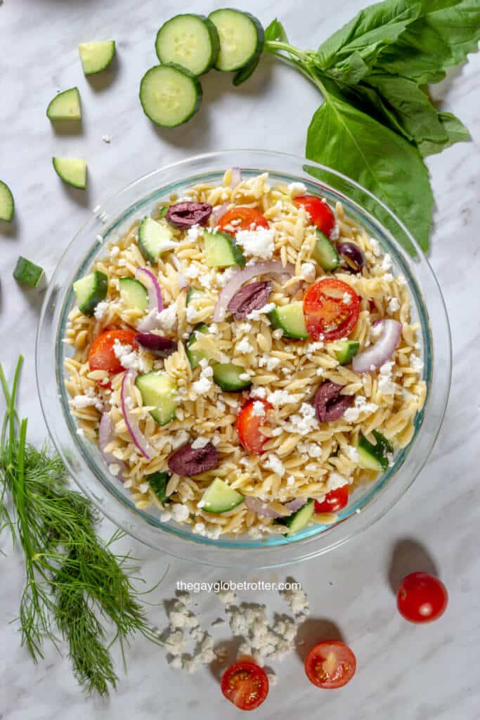 An overhead shot of Greek orzo pasta salad surrounded by dill, basil, cucumbers, and tomatoes.