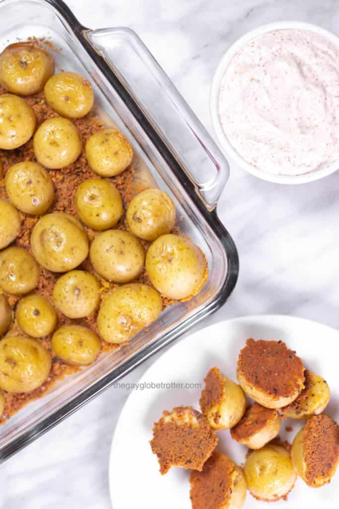 A dish of parmesan roasted potatoes fresh from the oven next to a plate and some dip.