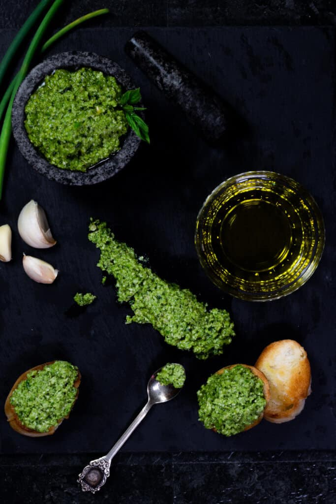 A flatlay of garlic scape pesto on a slate serving board