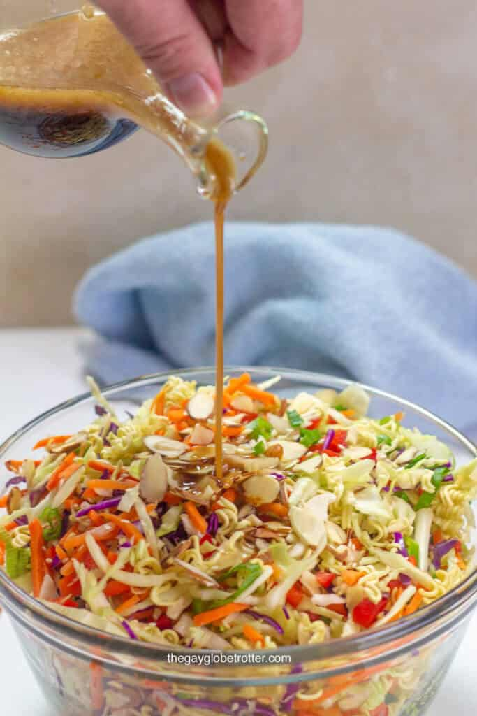 A serving bowl of ramen noodle salad with Asian sesame dressing being poured into it.