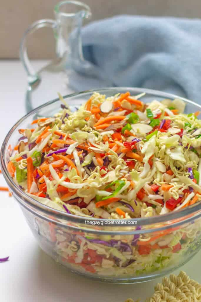 A clear serving bowl filled with ramen noodle salad.