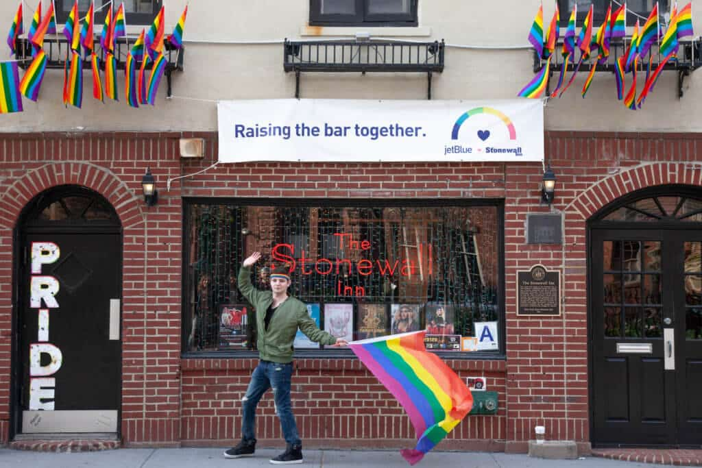 A man waving a rainbow flag in front of The Stonewall Inn.
