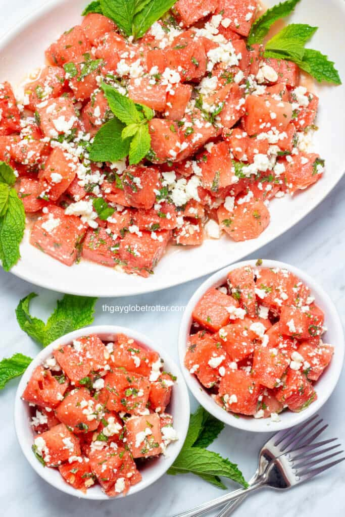 A serving platter of watermelon feta salad with two bowls full of salad next to it.
