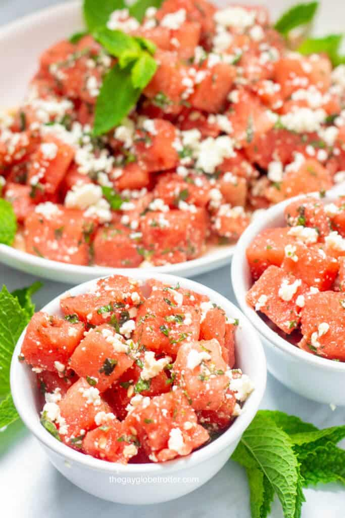 Two bowls of watermelon feta salad with a platter of it behind them.