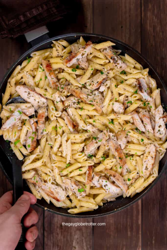 A hand scooping creamy pesto chicken pasta from a serving dish.