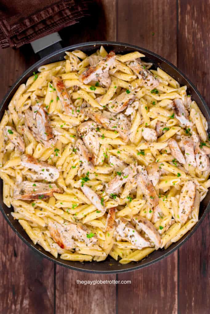 A pan full of creamy pesto pasta and chicken topped with fresh parsley.