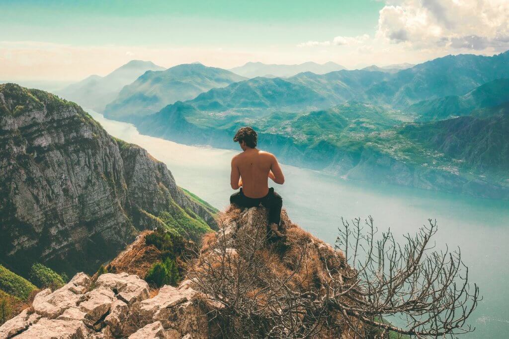 A man sitting on a cliff in Italy.
