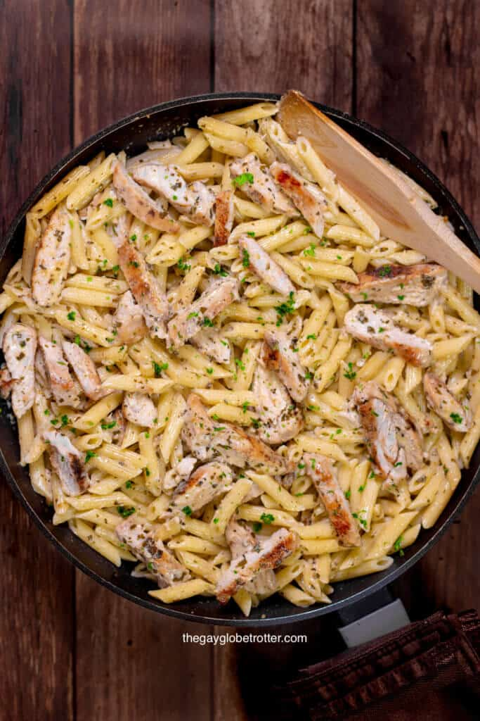 A pot full of creamy chicken pesto pasta with a wooden spoon.