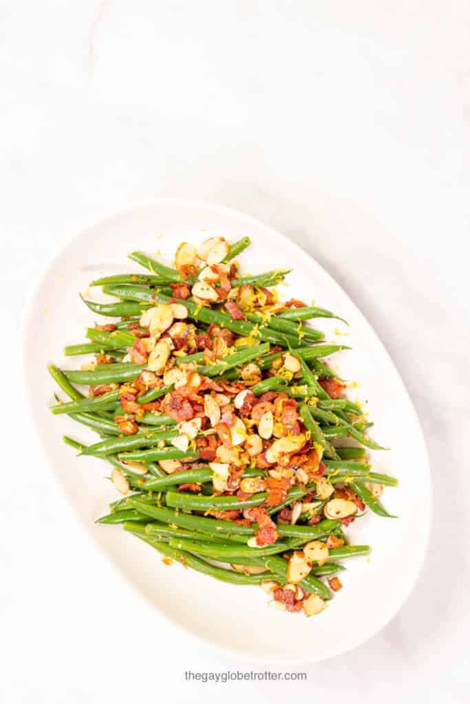 A serving platter full of fresh green beans almondine.