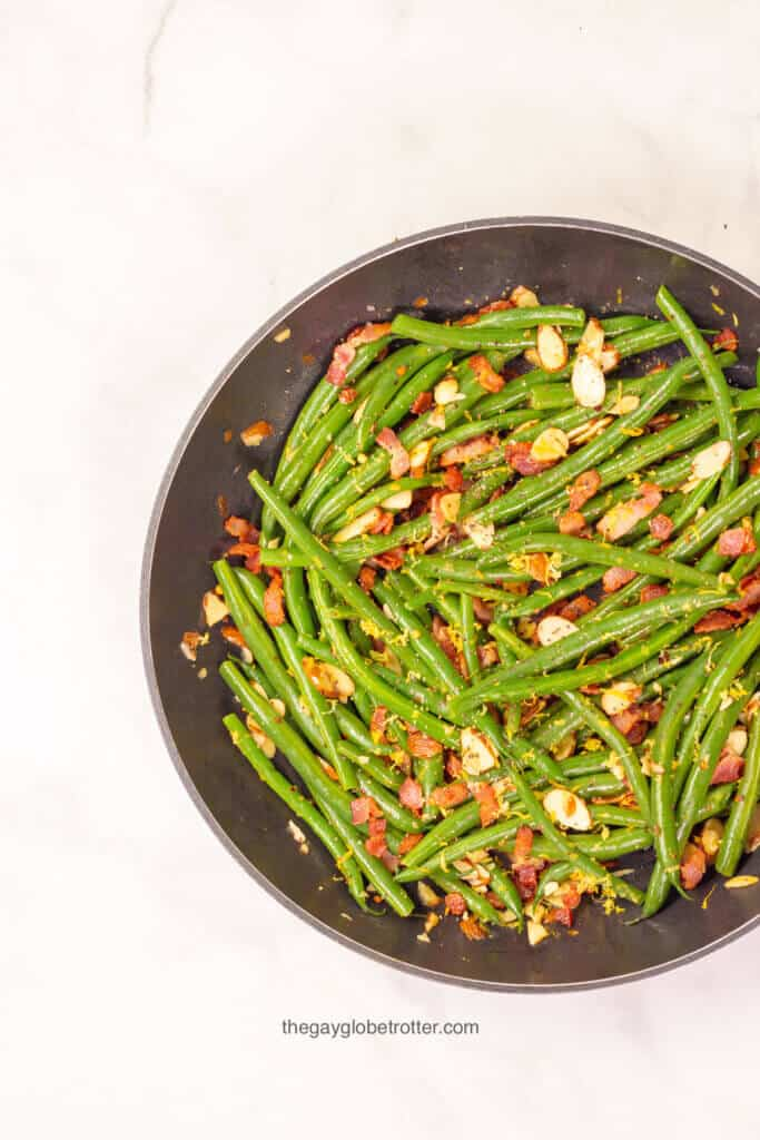 A sauce pan filled with green beans, almonds, and bacon.