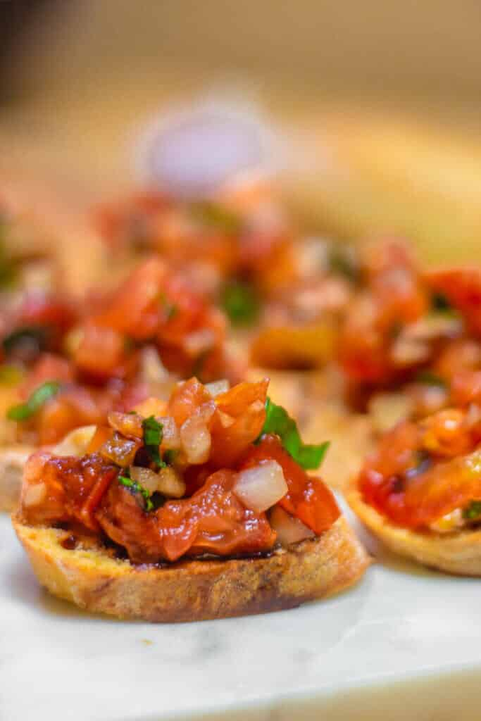Bruschetta on crostini on a serving board with fresh basil.