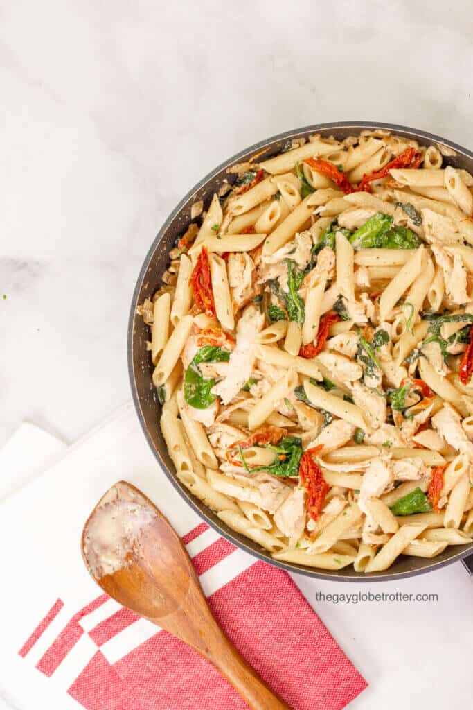 A pan of tuscan chicken pasta next to a wooden spoon that has just stirred the pasta.