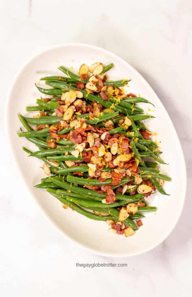 A serving platter with green beans almondine with bacon.