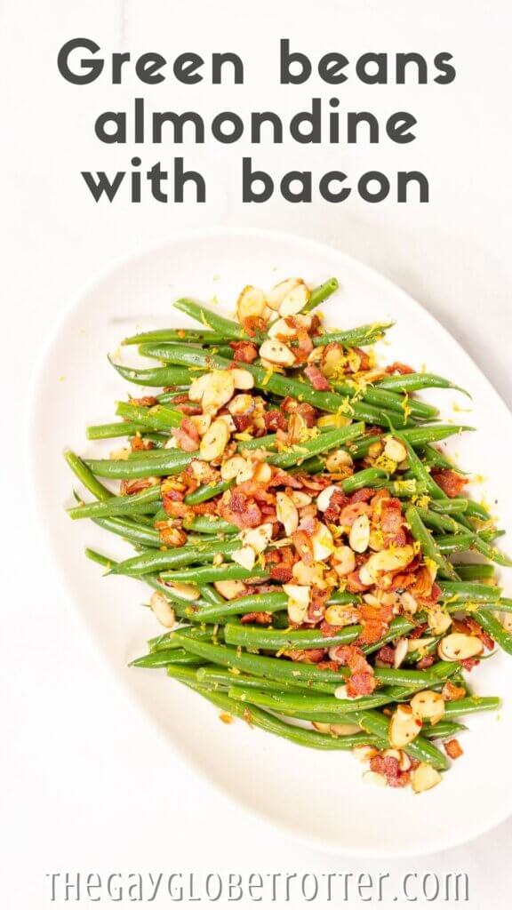 "A platter of green beans almondine with text overlay that reads ""green beans almondine with bacon""."