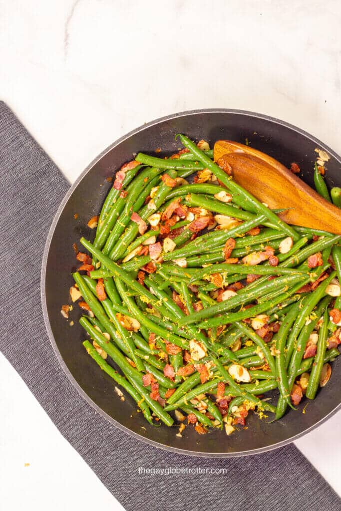 A pan full of green beans almondine with a wooden spoon.