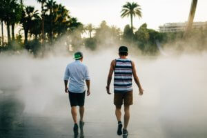 Two men walking towards fountain in tropics