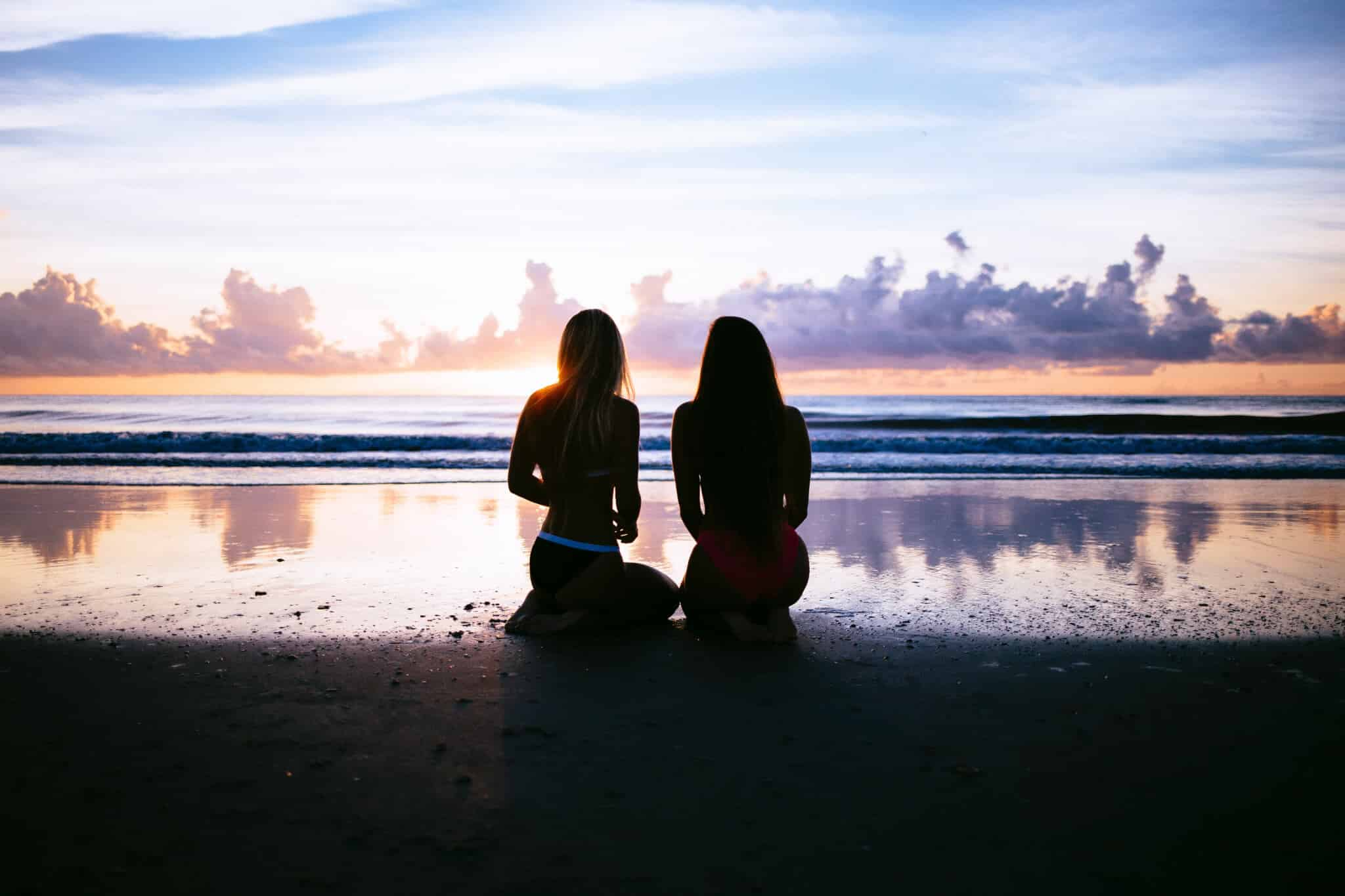 Two silhouetted women sitting on a beach
