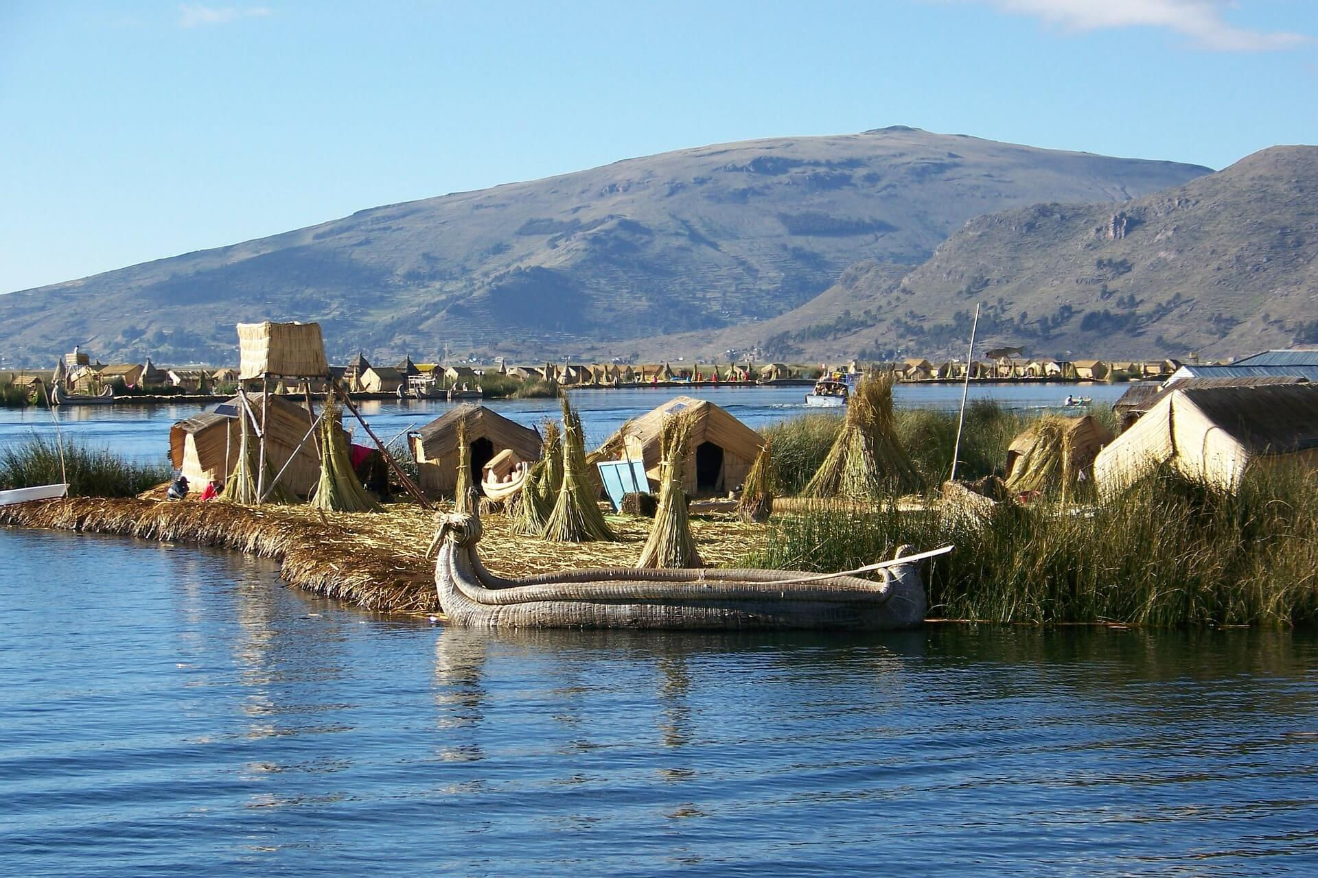 A boat floating on Lake Titicaca in Peru near hay huts