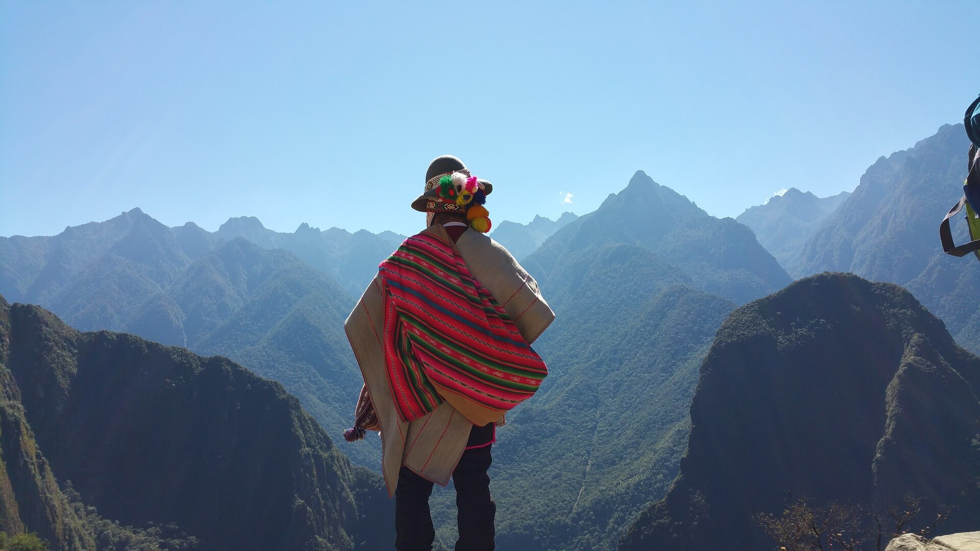 A Peruvian man looking out at the Andes mountains