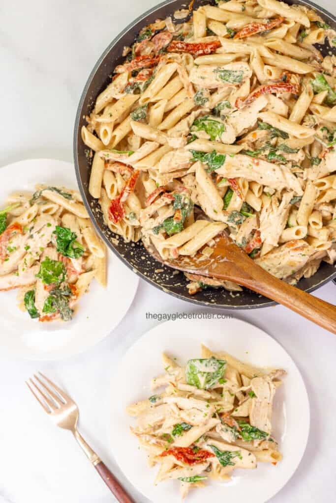 Tuscan chicken pasta being served from a pan to two serving plates.