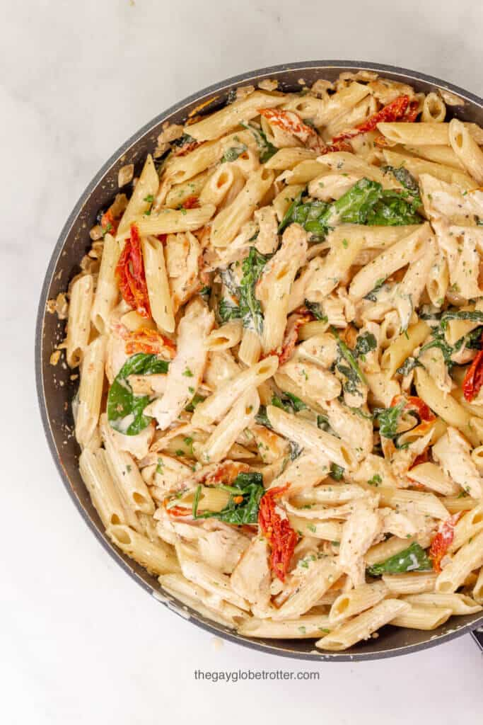 An overhead shot of a pan of tuscan chicken pasta with spinach, sun dried tomatoes, and chicken.