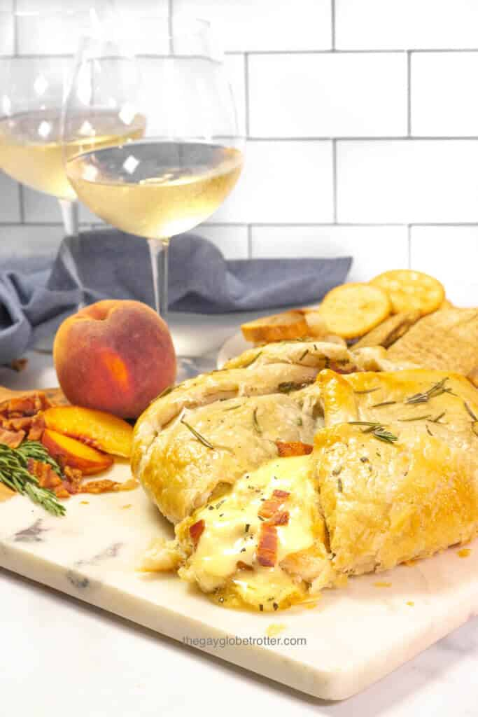 A serving platter with rosemary bacon peach brie en croute sliced open.