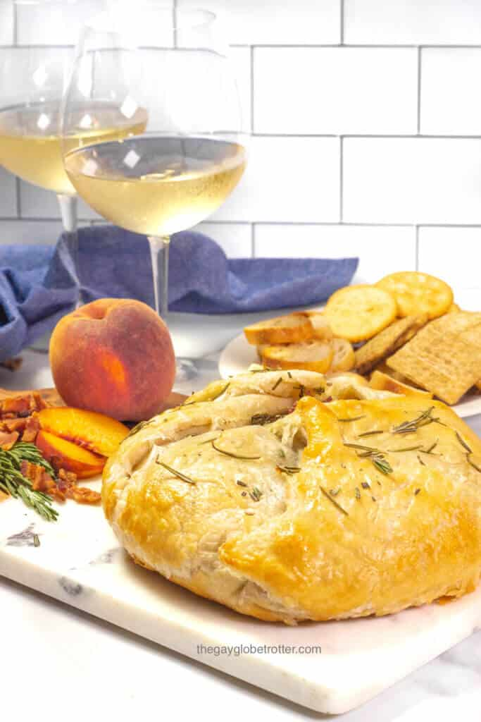 Baked brie en croute fresh from the oven topped with rosemary.