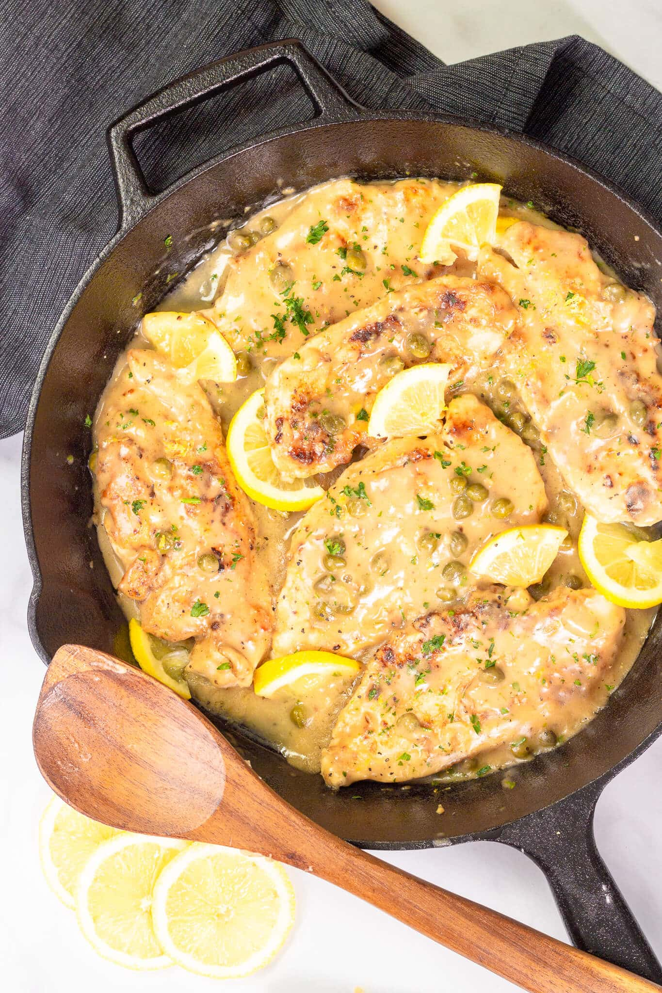 Lemon chicken piccata in a cast iron serving dish.