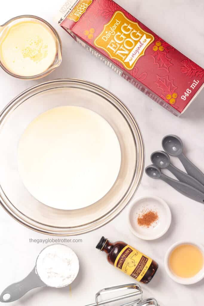 Ingredients to make eggnog whipped cream like vanilla, rum, eggnog, and heavy cream.