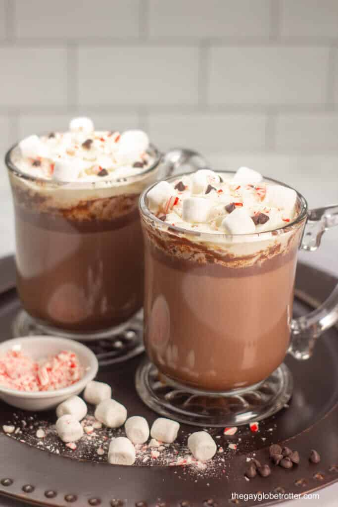 Two cups of homemade hot chocolate on a serving tray with marshmallows and candy cane pieces.