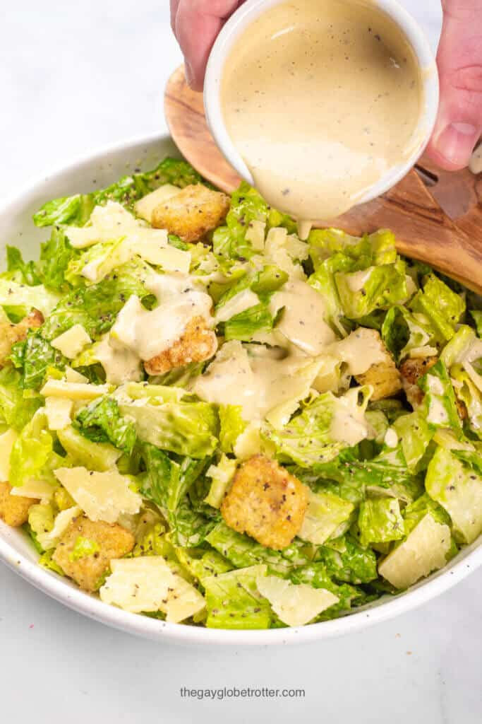 Caesar salad dressing being poured over caesar salad.