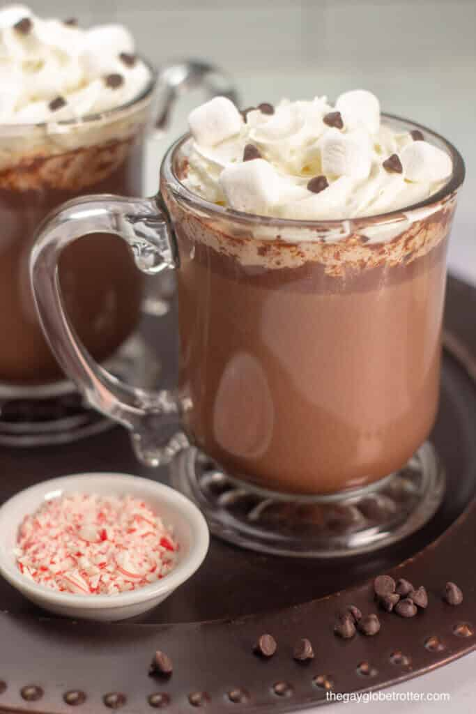 A cup of homemade hot chocolate topped with whipped cream, marshmallows, and chocolate chips.
