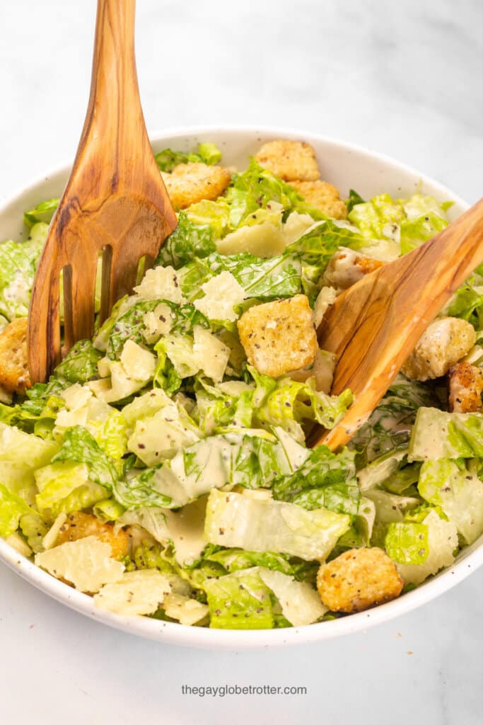 A caesar salad being tossed in a serving bowl with parmesan cheese and croutons.